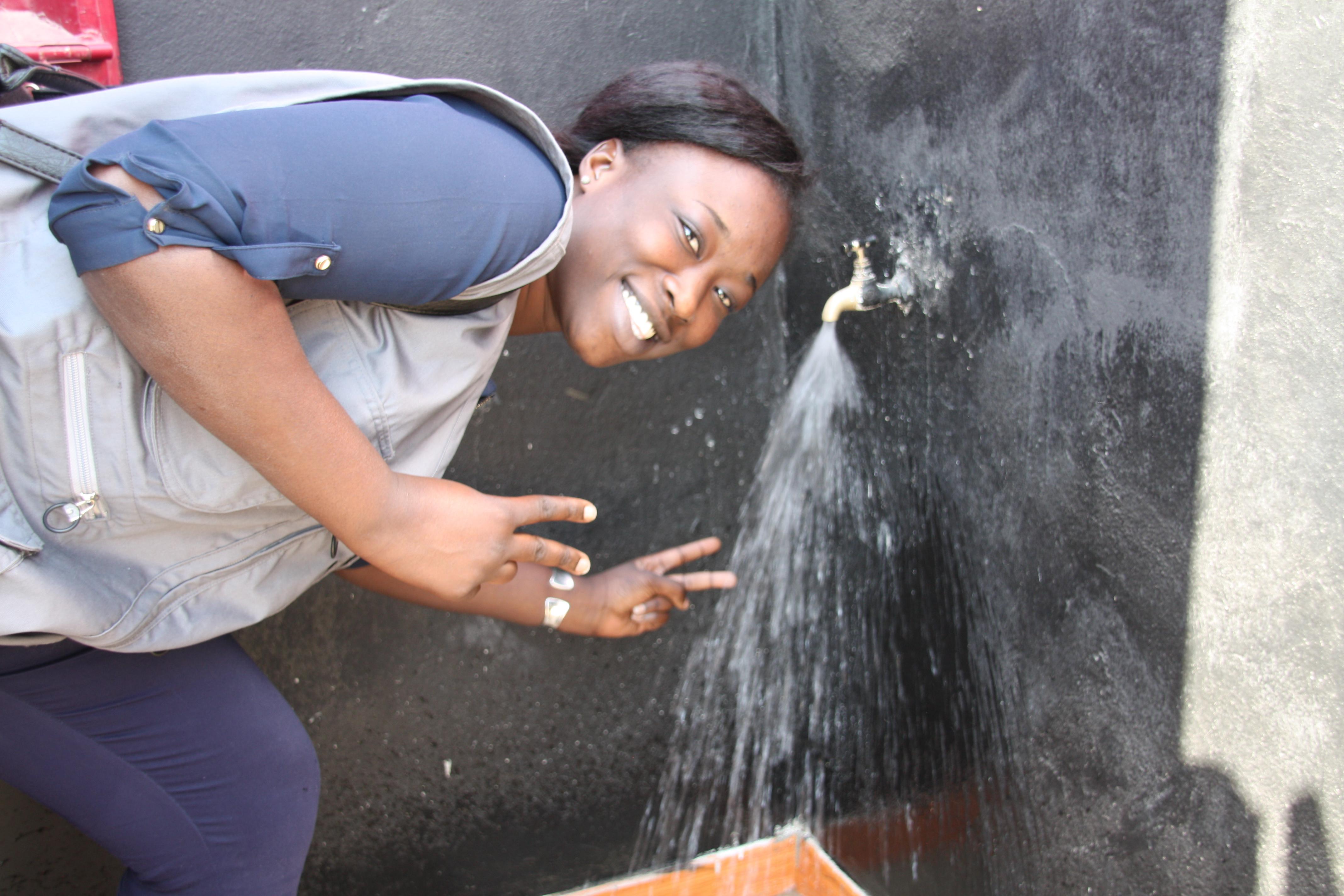 Fatou Ndiaye, chargée de suivi évaluation AMREF Afrique de l'ouest teste la borne fontaine
